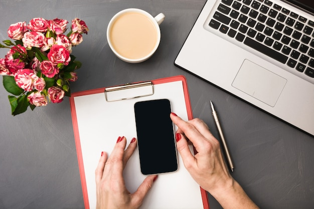 Bouquet di rose, tazza di caffè, mani femminili con smartphone e laptop su grigio