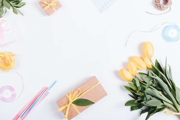 Bouquet di tulipani gialli, scatole con regali, nastri e corda su un tavolo bianco, vista dall'alto