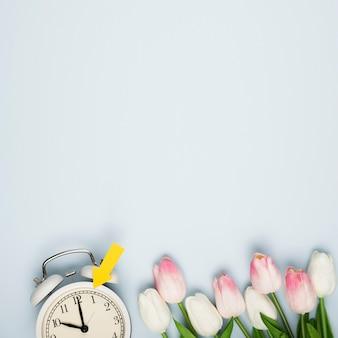 Bouquet di tulipani piatti laici accanto all'orologio