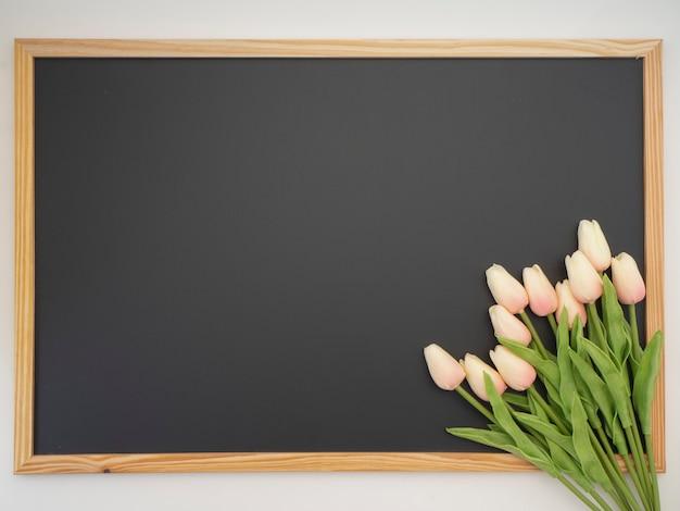 Bouquet di tulipani posto sulla cornice della lavagna