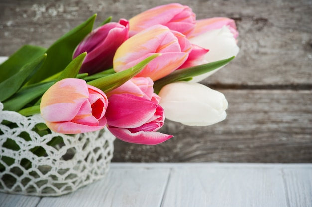 Bouquet di tulipani rosa nel cestino all'uncinetto