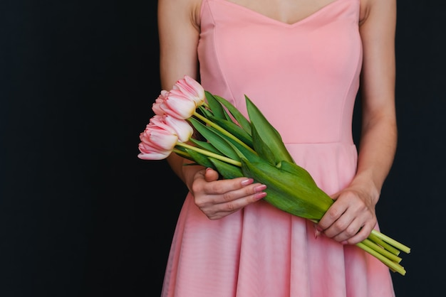 Bouquet di tulipani rosa nelle mani delle donne