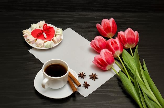 Bouquet di tulipani rosa, una tazza di caffè, biscotti rossi a forma di cuore con una nota, cannella, anice stellato e foglio di carta su legno nero