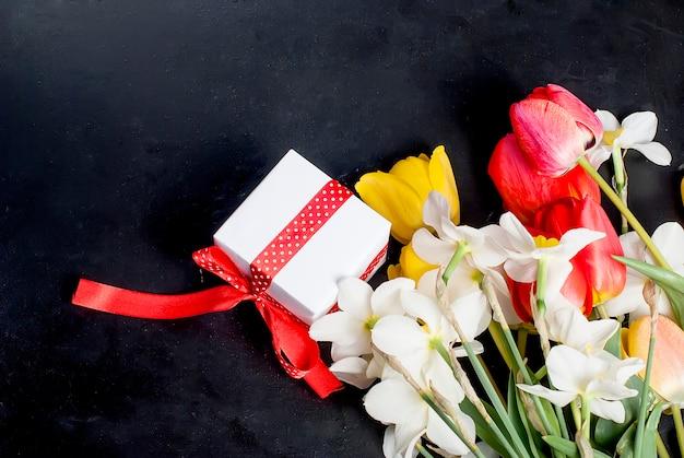 Bouquet di tulipani rossi, daffodils e regalo sullo sfondo nero