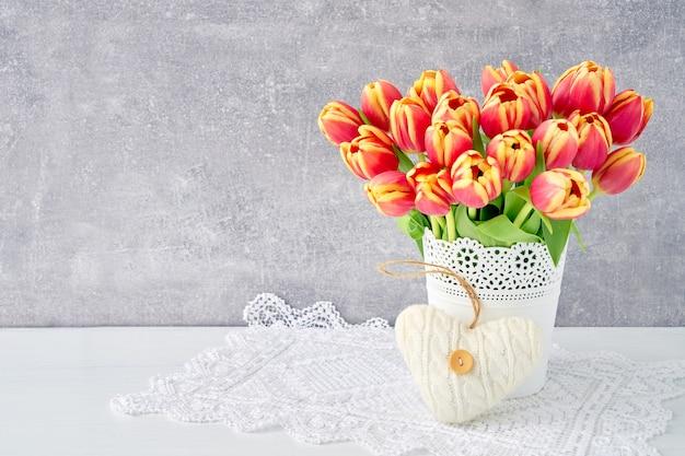 Bouquet di tulipani rossi in vaso decorato con cuore. san valentino, festa della mamma, concetto di compleanno.
