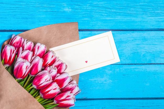 Bouquet di tulipani rossi per la festa delle donne giorno e san valentino sullo sfondo di tavole di legno.