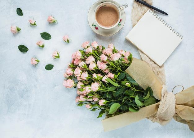 Bouquet fresco di rose rosa con una tazza di caffè; blocco note a spirale e penna su sfondo con texture