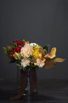 Bouquet in stile vintage in un vaso di vetro sul buio