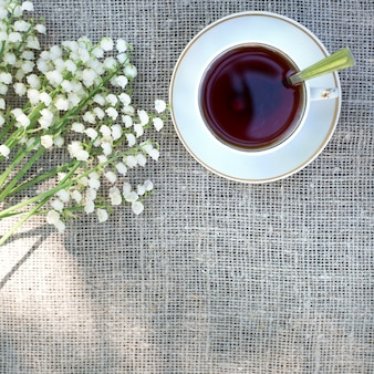 Bouquet primaverile di mughetti e una tazza di tè