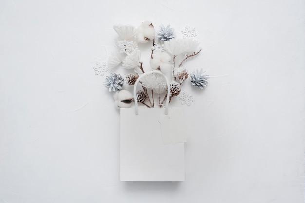 Bouquet secco di fiori di cotone, coni e fiocchi di neve sulla borsa bianca