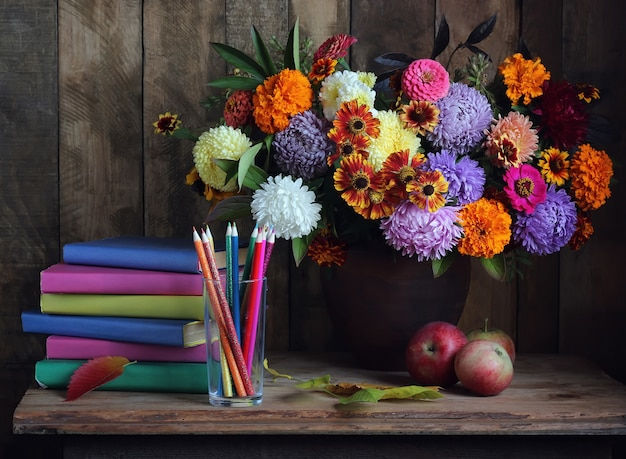Bouquet, una pila di libri e mele sul tavolo. di nuovo a scuola. il giorno dell'insegnante. il primo di settembre.