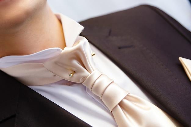 Boutonniere e cravatta a farfalla da vicino.