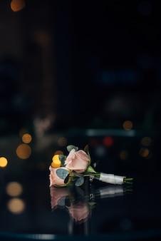Boutonniere per lo sposo di delicati fiori rosa su uno sfondo sfocato scuro