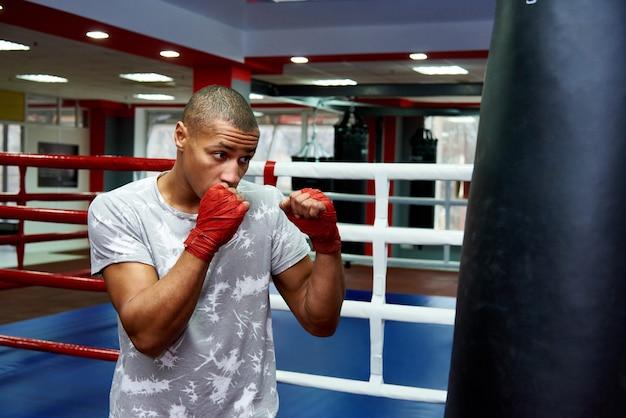 Boxer che colpisce un enorme sacco da boxe in uno studio di pugilato. boxer duro allenamento.