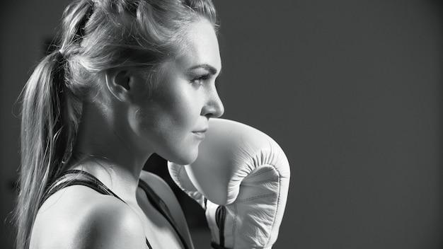 Boxer femmina la giovane donna si esercita nelle sue mosse di pugilato. intenso pugile lanciando pugili donna.