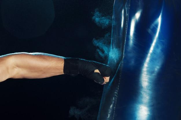 Boxer maschio nel sacco da boxe con drammatica illuminazione tagliente