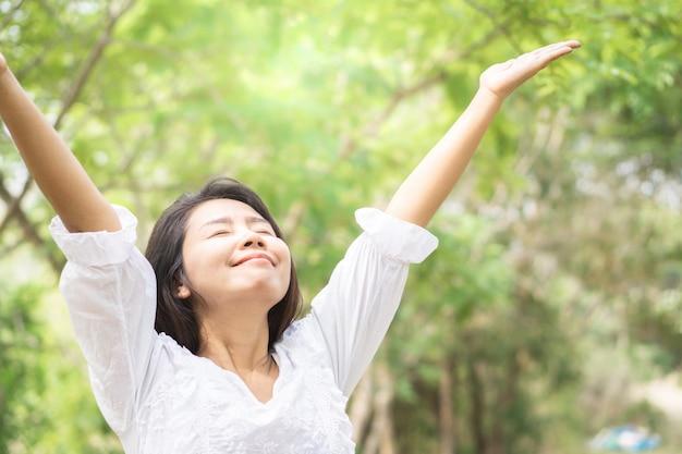 Braccia della donna asiatica felice respirazione fresca