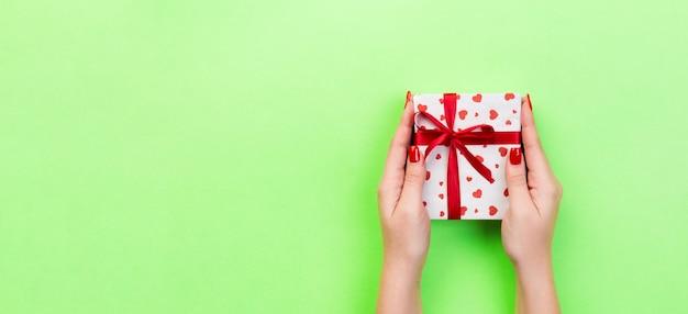 Braccia della donna che tengono il contenitore di regalo