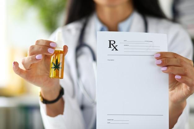 Braccia della dottoressa tenendo il barattolo contagocce di olio di cannabis concentrato