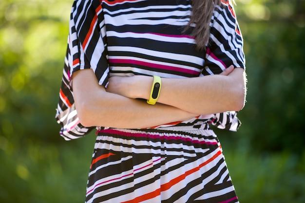 Braccia della giovane donna con il braccialetto di forma fisica sopra all'aperto