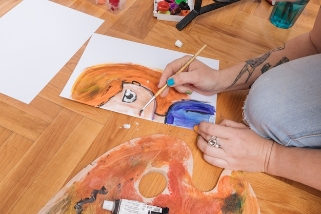 Braccia tatuate di donna che dipinge sul pavimento