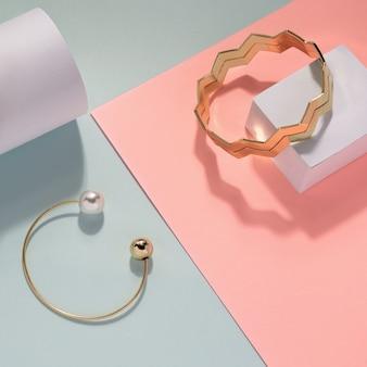 Bracciale in perle dorate e bracciale dorato a zigzag su fondo rosa e blu