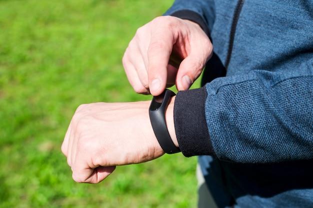 Braccialetto di fitness o orologio intelligente sulla mano di un uomo