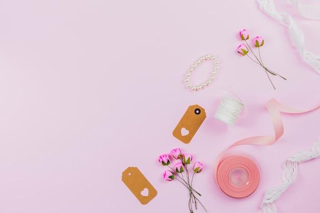 Braccialetto di perle; etichetta; nastro; rocchetto di filo; pizzi e rose artificiali su sfondo rosa