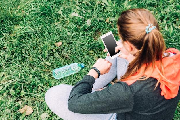 Braccialetto fitness a portata di mano e telefono cellulare su sfondo di erba