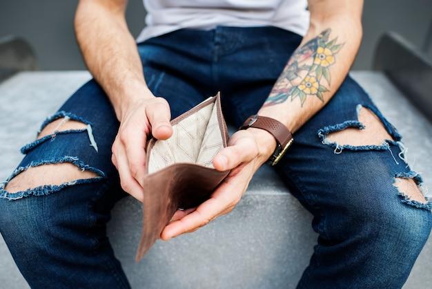 Braccio con il tatuaggio che tiene il portafoglio vuoto