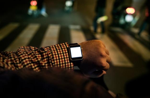 Braccio con orologio da polso digitale nelle ore notturne