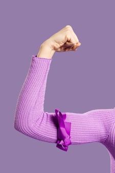 Braccio del muscolo del primo piano legato con il nastro viola