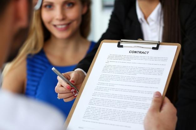 Braccio femminile offre forma di contratto sul blocco appunti