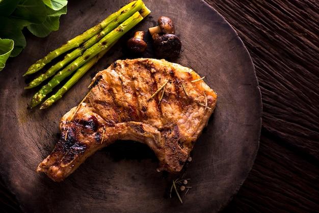 Braciola di maiale alla griglia con verdure su tavola di legno
