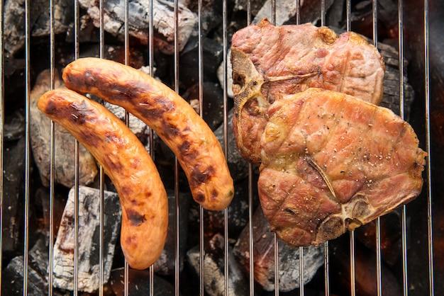 Braciola di maiale e salsiccia alla griglia sulla griglia ardente