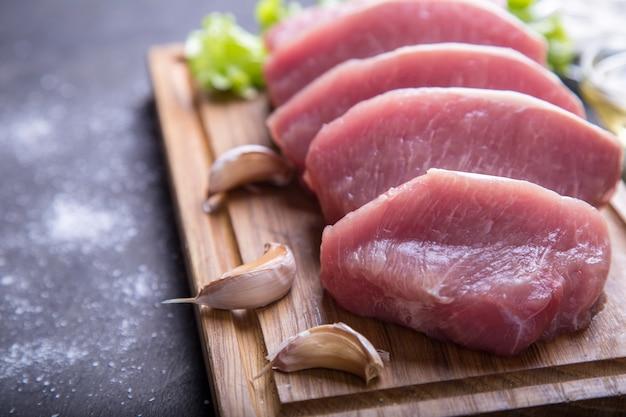 Braciole di maiale crude su un bordo di legno. la carne è pronta per la cottura