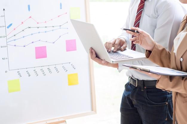 Brainstorming del gruppo di affari che discute i documenti di profitti di vendite