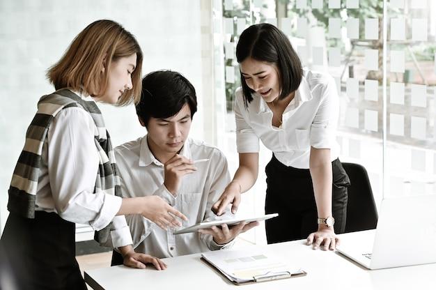 Brainstorming della giovane impresa con la compressa sul posto di lavoro dell'ufficio