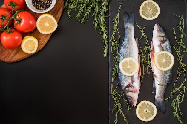 Branzino fresco, rosmarino, pomodoro, limone, pepe e spezie sul tavolo