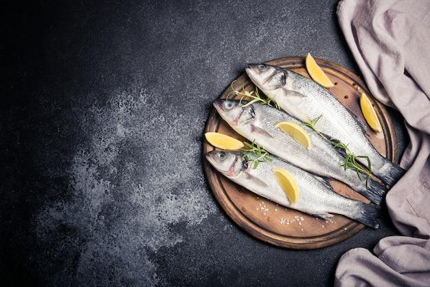 Branzino intero crudo fresco. pesce crudo della spigola con gli ingredienti delle erbe e delle spezie. vista dall'alto con copyspace.