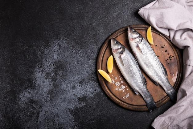 Branzino intero crudo fresco. pesce crudo della spigola con gli ingredienti delle erbe e delle spezie. vista dall'alto con spazio di copia.