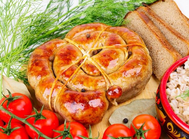 Bratwurst ad anello con pane, pomodori ed erbe