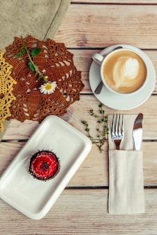 Breakfest con caffè e torta sulla tavola di legno con forchetta e coltello