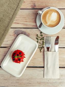 Breakfest con cappuccino e torta sulla tavola di legno con forchetta e coltello