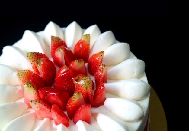 Breve torta appetitosa della vaniglia della fragola fresca su fondo nero