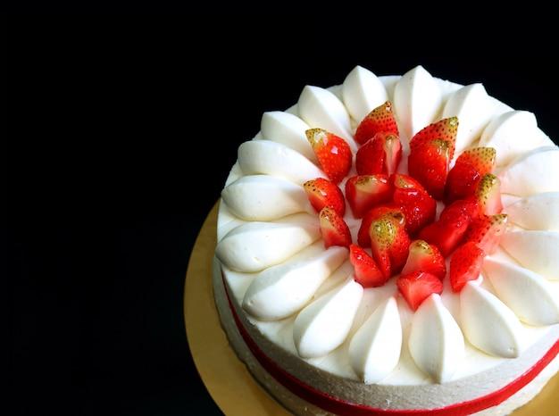 Breve torta mouthwatering della vaniglia della fragola fresca isolata su fondo nero