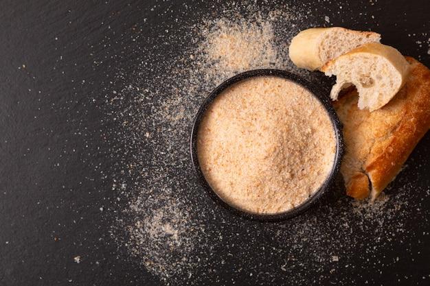 Briciole di pane organiche casalinghe degli ingredienti alimentari in ciotola ceramica nera sul bordo nero dell'ardesia