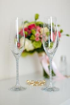 Bridal bellissimo bouquet romantico di vari fiori, bicchieri per champagne, pietre brillanti, una forcina d'oro, orecchini. messa a fuoco selettiva.