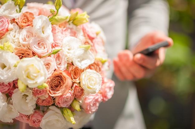 Bridal bouquet di fiori un uomo con un mazzo di fiori e un telefono è in attesa di una donna ad un appuntamento.