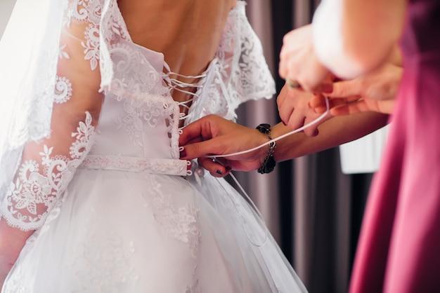 Bridesmaids allacciano abito bianco da sposa sulla schiena della sposa